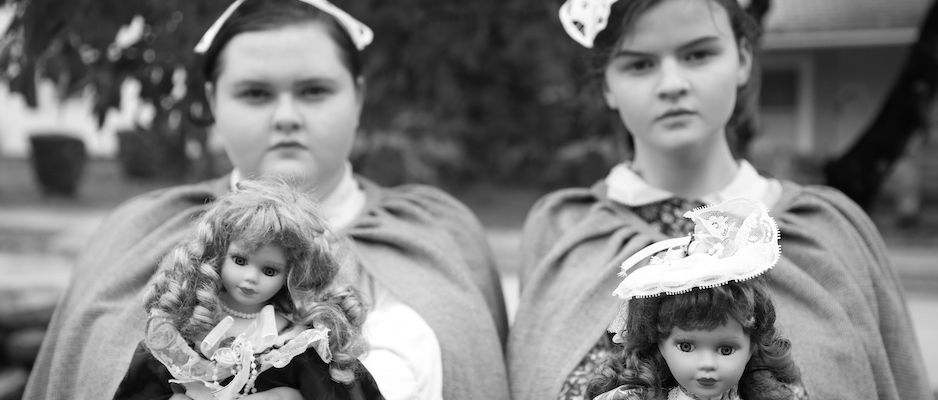 Two ghost girls holding dolls
